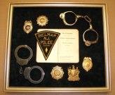 Belmar police shadowbox including antique handcuffs.